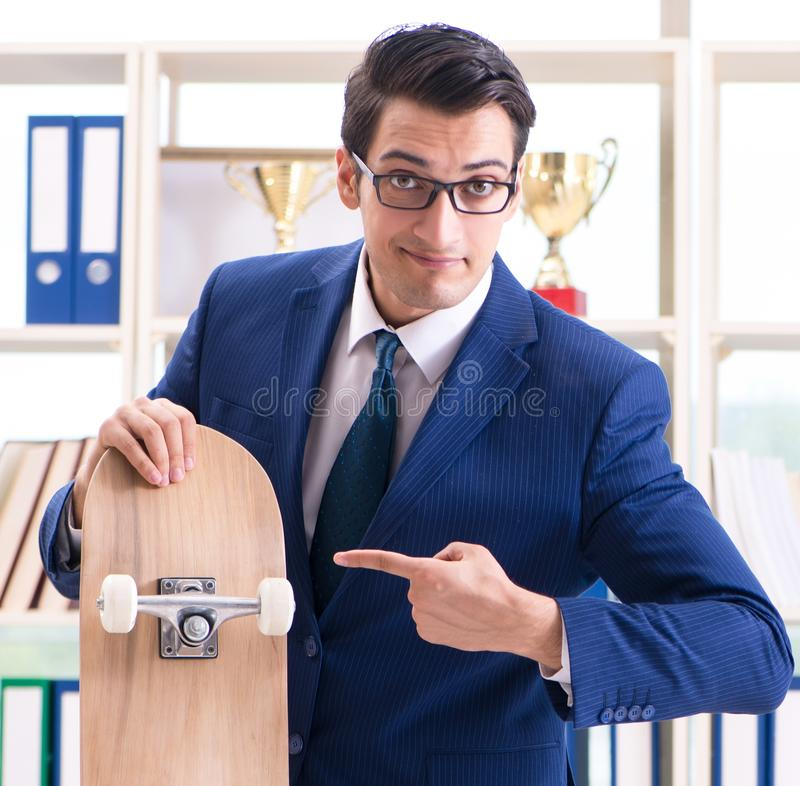 Businessman with skateboard in office. The businessman with skateboard in office stock photography