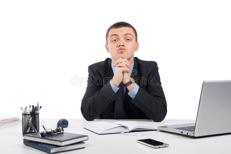 Businessman skeptically looking at you sitting at his desk royalty free stock image