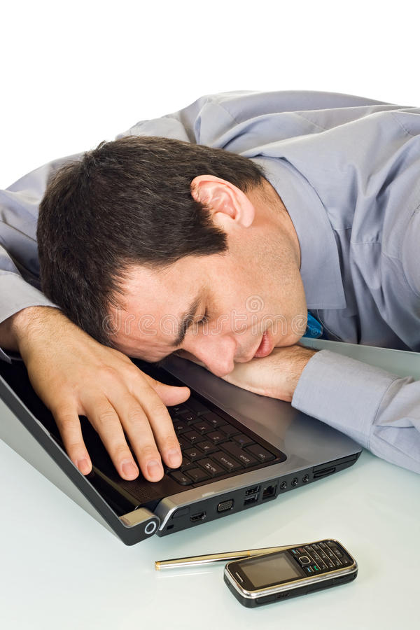 Businessman sleeping. Tired businessman sleeping in the office, he putting his head onto keyboard of the laptop - isolated royalty free stock photography