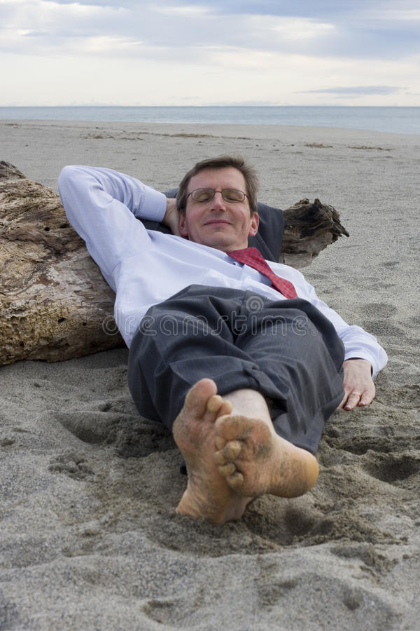 Businessman sleeping on a beach. With a smile on his face stock images