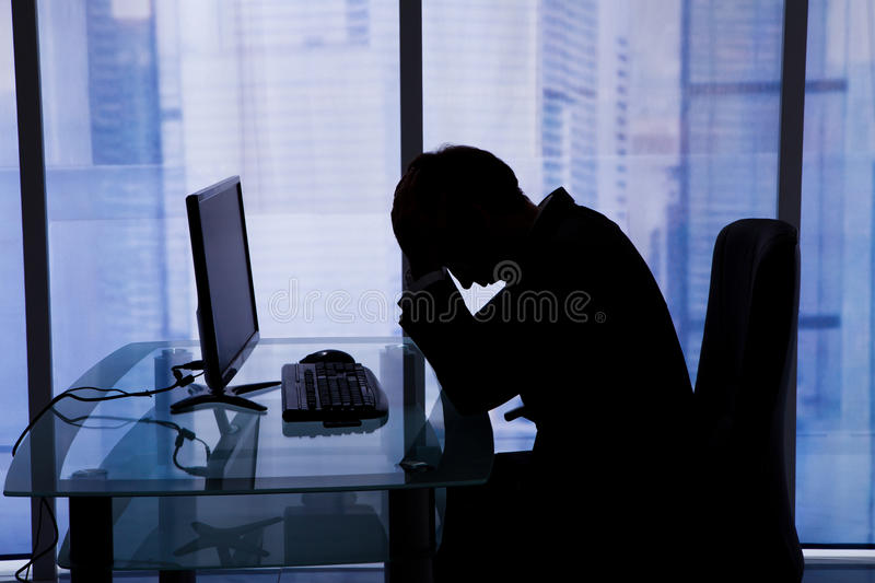 Businessman sleeping at computer desk in office. Side view of tired young businessman sleeping at computer desk in office stock photography
