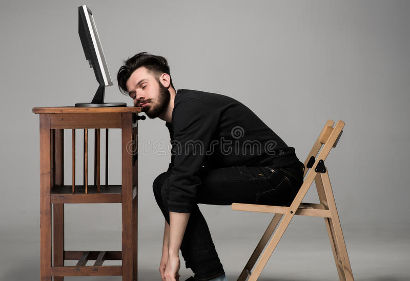 Businessman sleeping on a computer. Businessman sleeping near monitor of computer on gray background royalty free stock photo