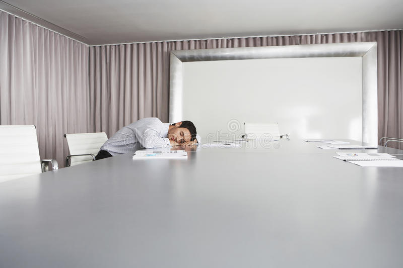 Businessman Sleeping In Conference Room stock photography