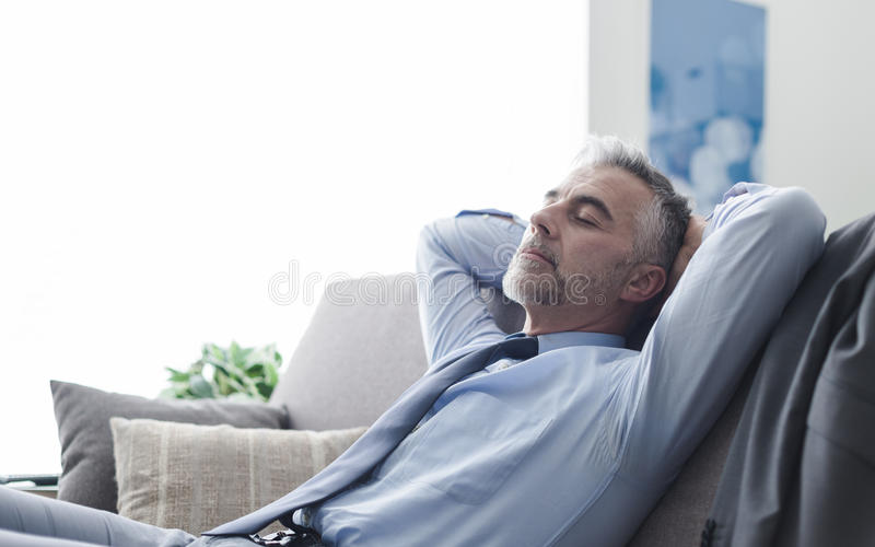 Businessman sleeping on the couch. Handsome businessman relaxing at home on the couch, he is sleeping with hands behind head stock photo