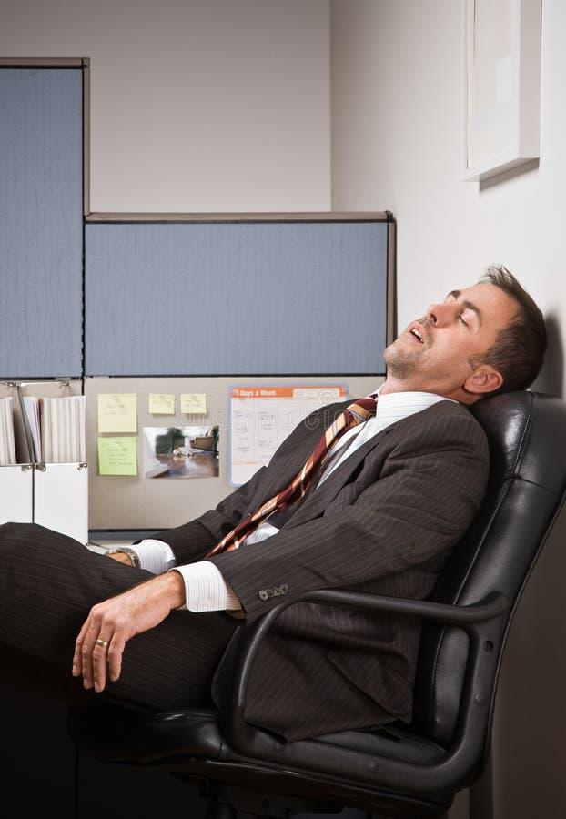 Businessman sleeping at desk. Businessman sleeping in his cubicle royalty free stock image