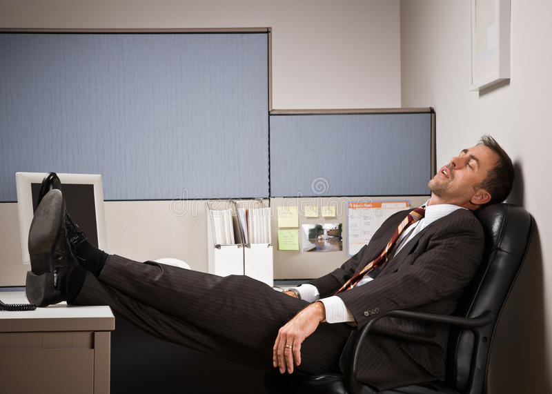 Businessman sleeping at desk with feet up. Businessman sleeping at a desk with his feet up royalty free stock photo
