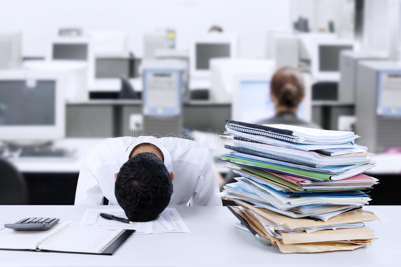 Businessman sleeping at desk. Tired young businessman is sleeping at desk in office stock images
