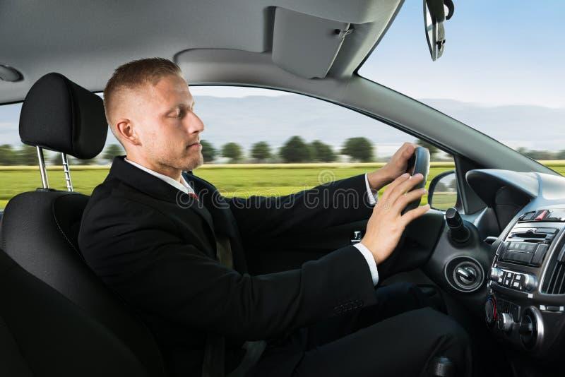 Businessman sleeping while driving car. Portrait Of A Young Businessman Sleeping While Driving Car stock photos
