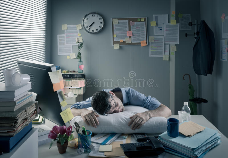 Businessman sleeping in the office overnight stock image