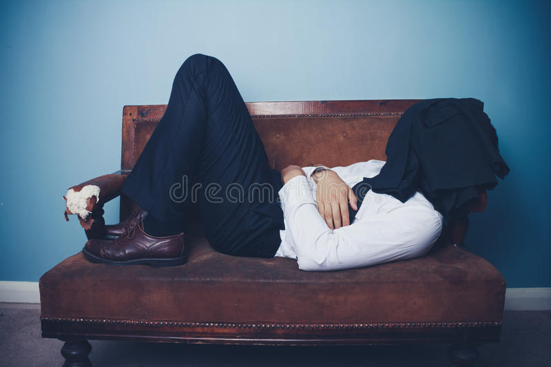 Businessman sleeping on old sofa. Businessman is sleeping on an old sofa with his jacket over his face royalty free stock photo