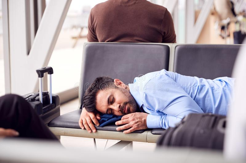Businessman Sleeping On Seats In Airport Departure Lounge Because Of Delay stock photos