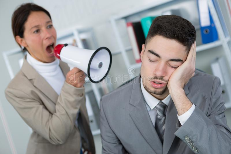 Businessman sleeping at workplace and businesswoman waking him up stock photography