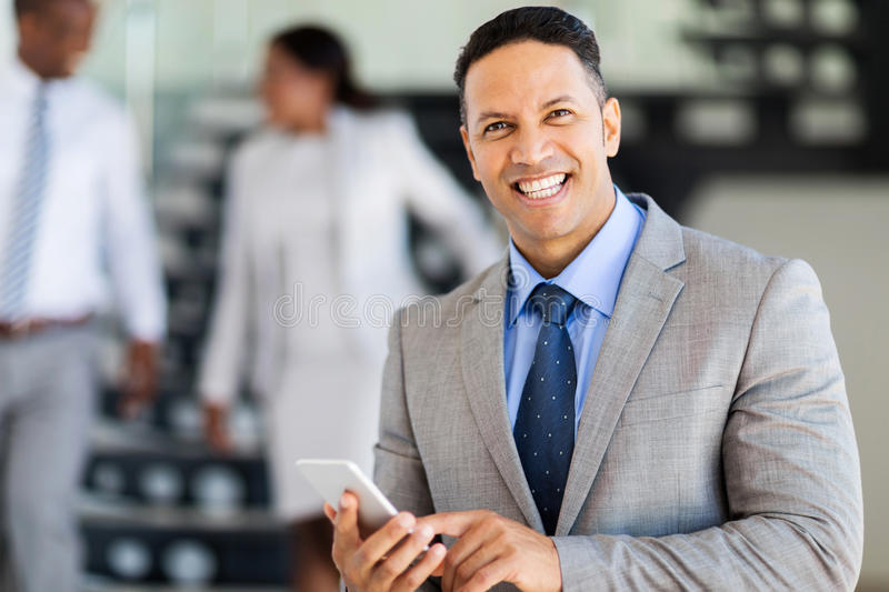 Businessman smart phone. Smiling middle aged businessman using smart phone royalty free stock photo