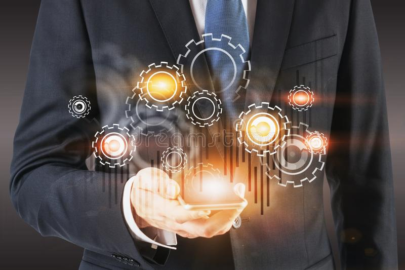 Businessman with smartphone, gears and graph. Unrecognizable businessman looking at smartphone screen with double exposure of gears and graph. Concept of royalty free stock image