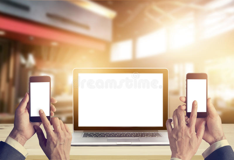 Businessman with smartphone in hands and laptop computer blank screen stock images