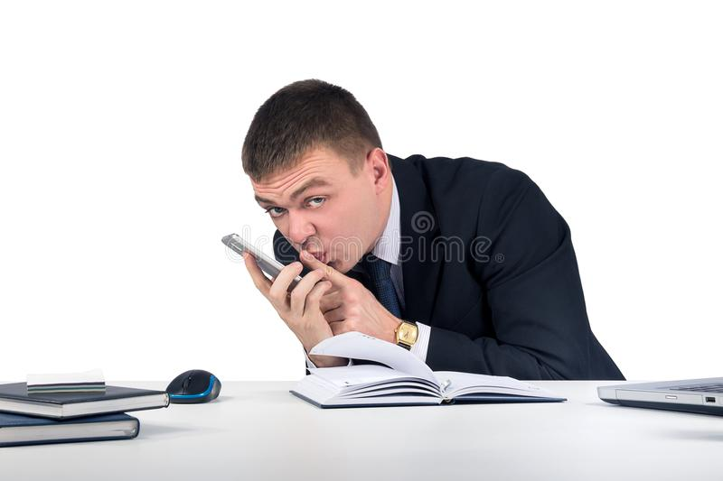 Businessman with smartphone holding his finger in front of his mouth and making silence gesture royalty free stock photography