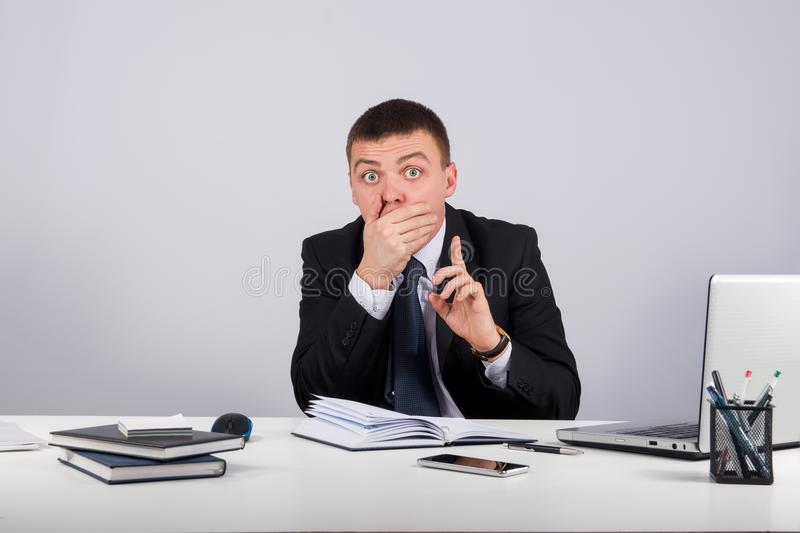 Businessman with smartphone holding his finger in front of his mouth and making silence gesture shh stock images