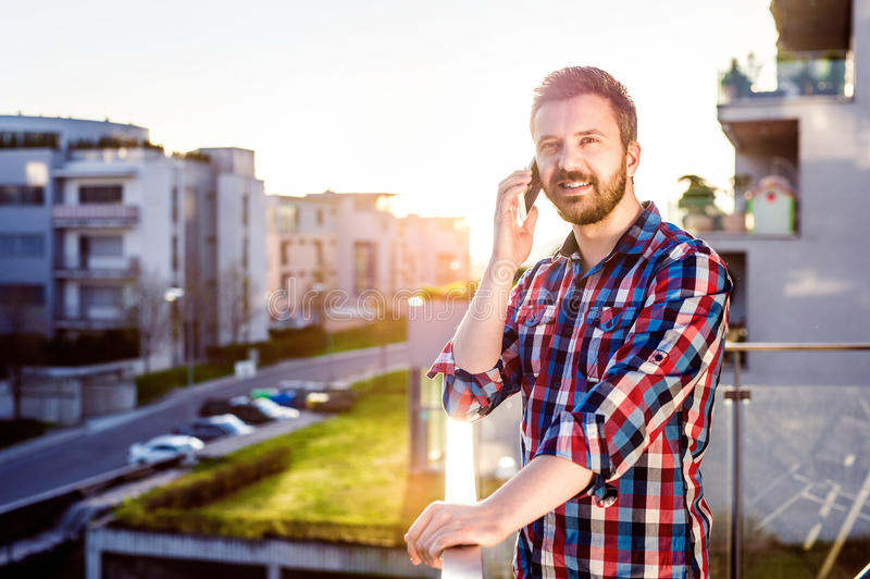 Businessman with smartphone making phone call, standing on balco. Hipster businessman in checked shirt with smart phone making a phone call, standing on balcony stock photos