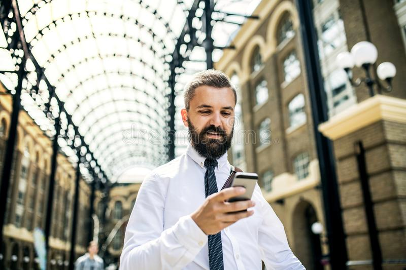 Businessman with smartphone on the trian station in London, text messaging. stock photography