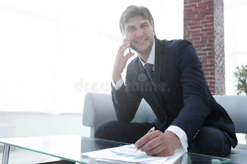 Businessman with a smartphone in the workplace royalty free stock photo