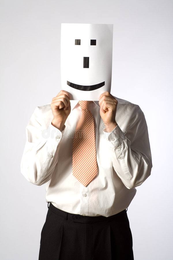Businessman smiley emoticon. A businessman holding a white paper with an emoticon smiley face over his own face royalty free stock photos