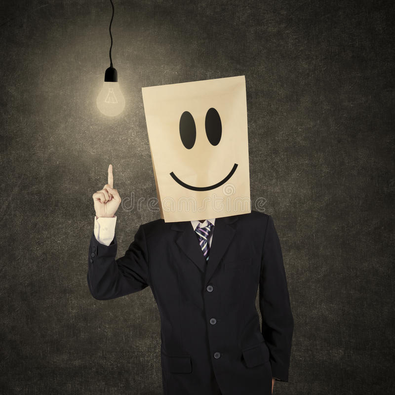 Businessman with smiley emoticon having idea 1. Businessman with cardboard head having a bright idea while pointing at bright lightbulb royalty free stock photos
