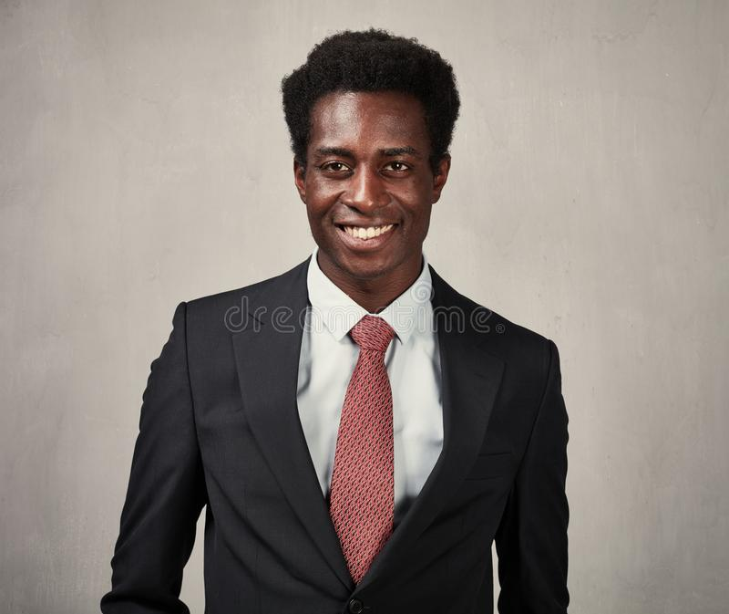 Businessman. Smiling black businessman over gray wall background stock images