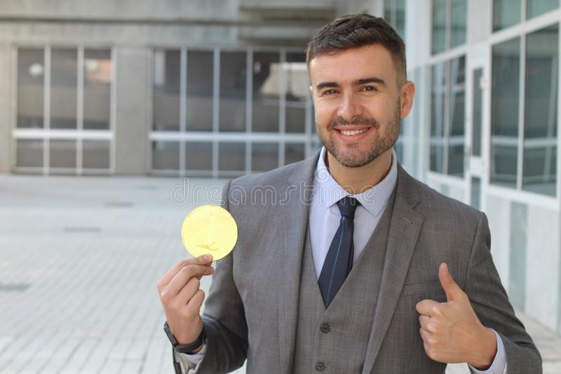 Businessman smiling while holding a big coin.  stock photos