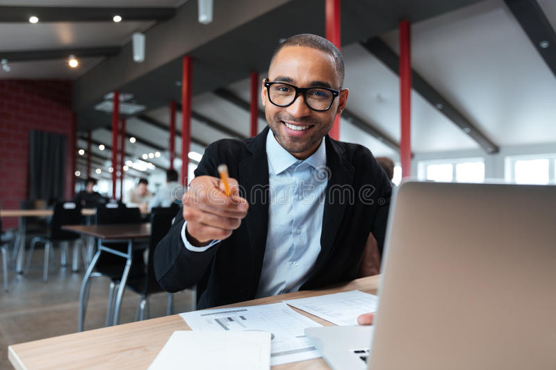 Businessman smiling and pointing at the working place. Businessman smiling and pointing with pncil at the working place royalty free stock image
