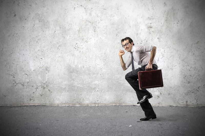 Businessman smiling and running fast stock image