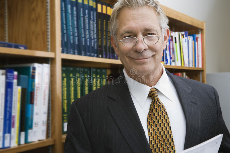 Businessman Smiling While Standing In Library