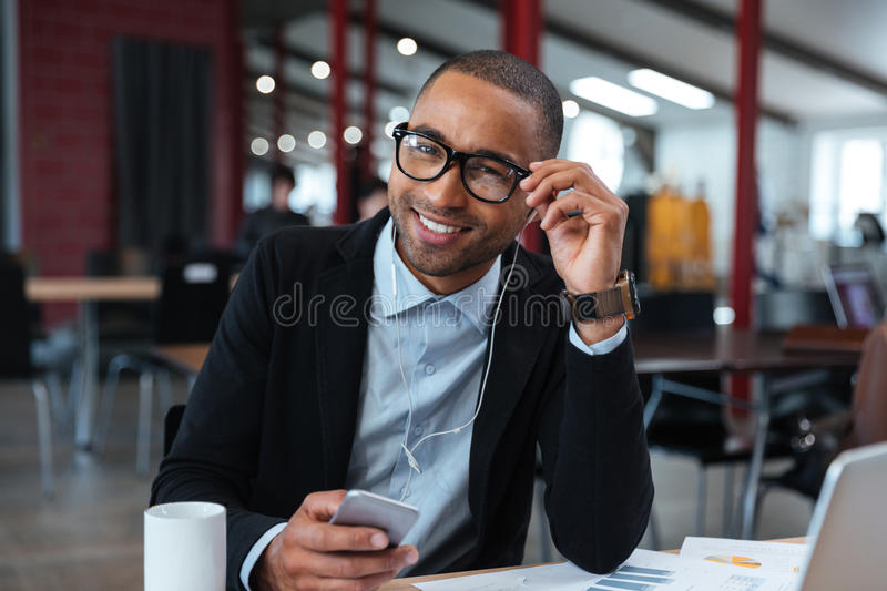 Businessman smiling and touching his glasses. At the laptop royalty free stock image