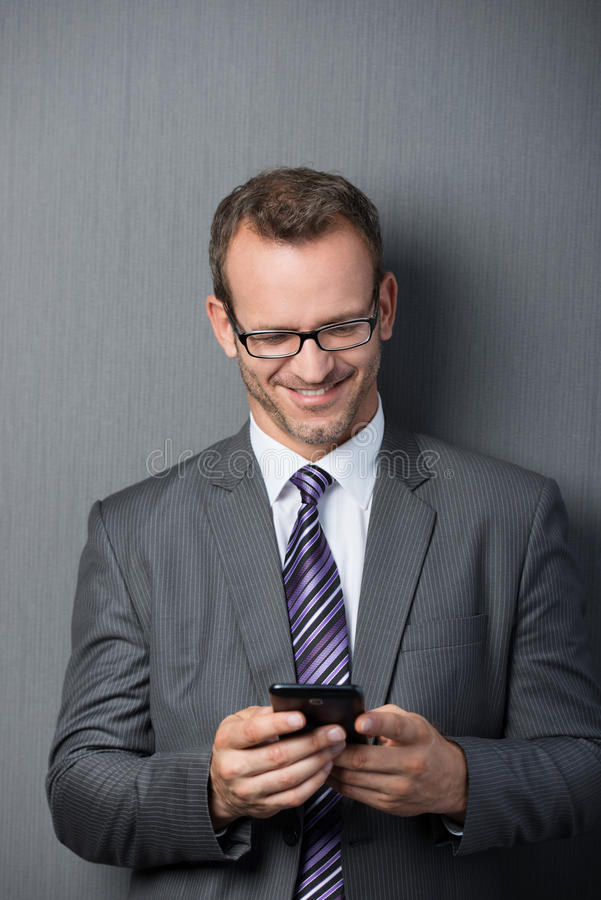 Businessman smiling while using the smartphone stock photo