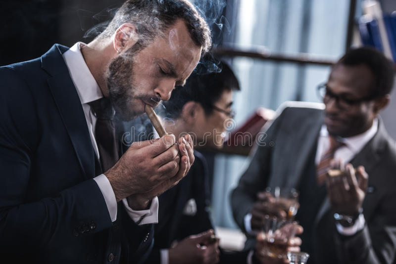 Businessman smoking cigar with multicultural business team royalty free stock photo