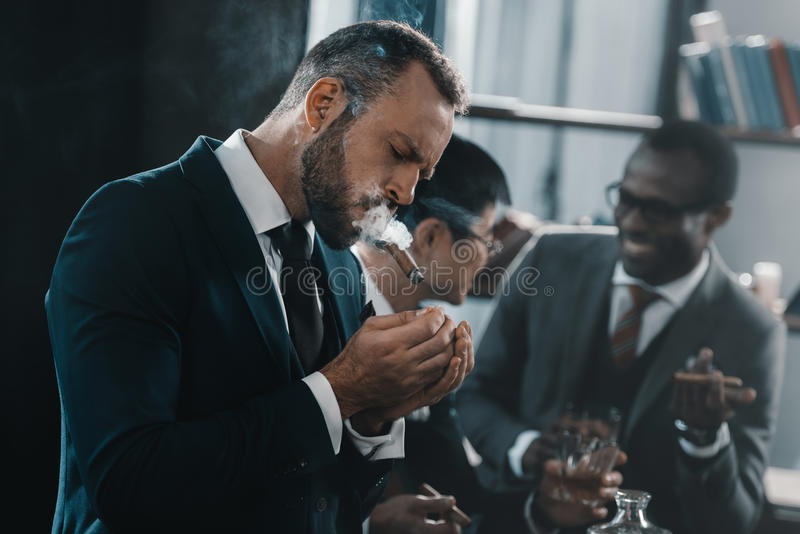 Businessman smoking cigar with multicultural business team stock image
