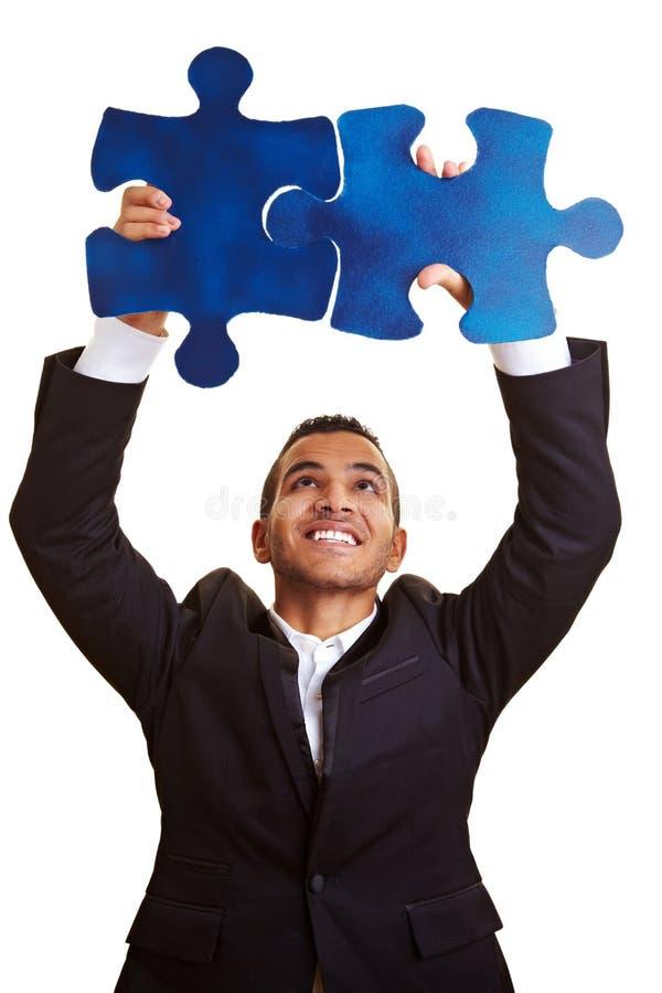 Businessman solving huge jigsaw stock image