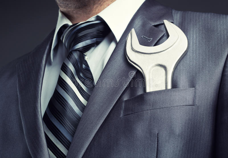 Businessman with spanner. In suit pocket stock images
