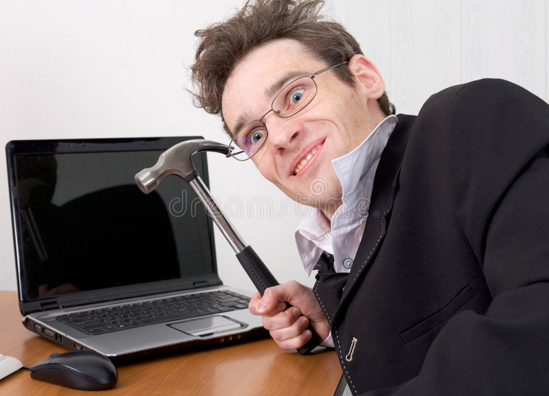 Businessman in spectacles gone mad with a hammer royalty free stock images