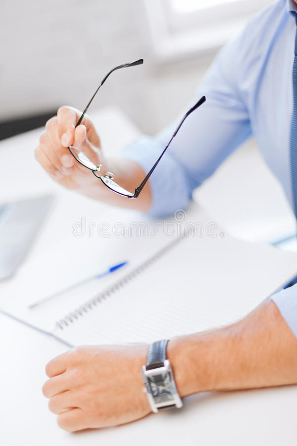 Businessman With Spectacles Writing In Notebook Royalty Free Stock Photography
