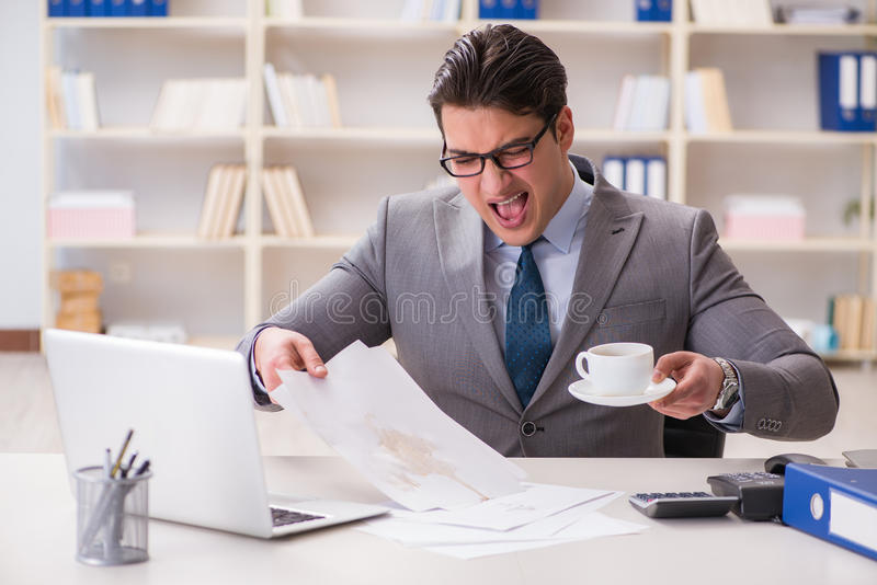 The businessman spilling coffee on important documents. Businessman spilling coffee on important documents royalty free stock photo
