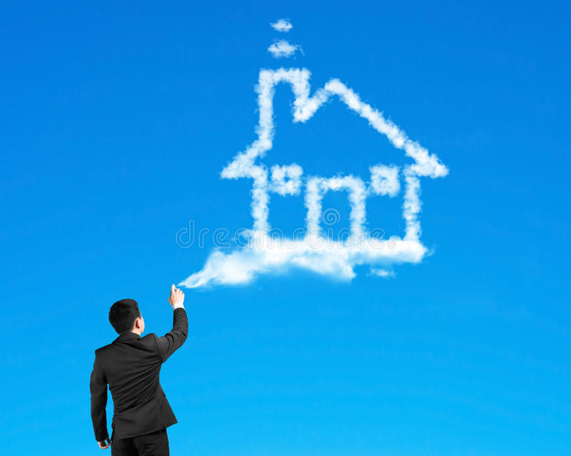 Businessman spraying house shape cloud paint with blue sky. Background stock images