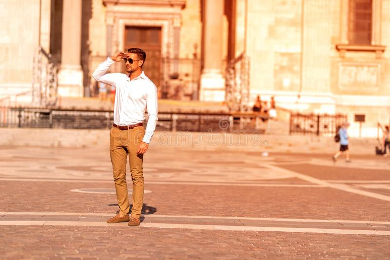 A businessman on a square covering his face. A handsome young businessman standing on a square and covering his face on a sunny day royalty free stock image