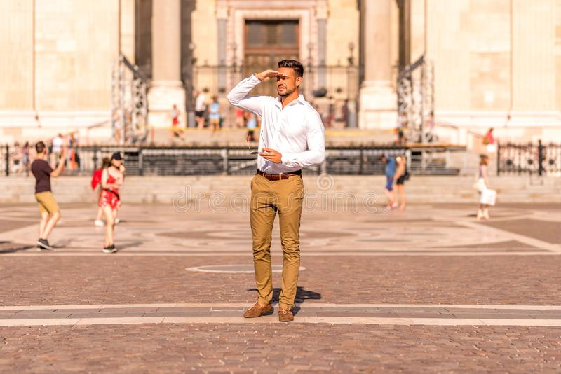 A businessman on a square covering his face. A handsome young businessman standing on a square and covering his face on a sunny day royalty free stock photos