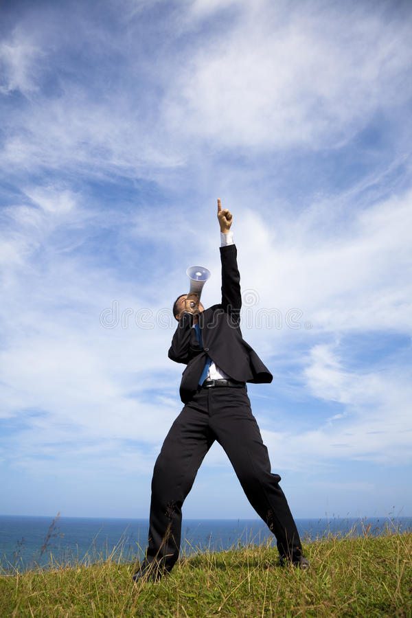 Businessman stand on the hill and holding megaphone royalty free stock photo