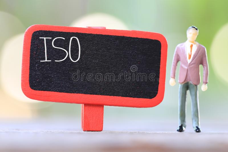 Businessman stand near wooden sign of ISO Text. Businessman stand near wooden sign of ISO Text in Concept of quality management system stock image