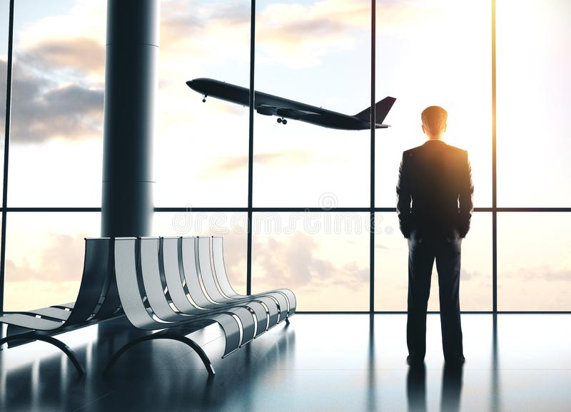 Businessman standing in airport. And looking at airplane flying in sky. Travel and transportation concept stock images
