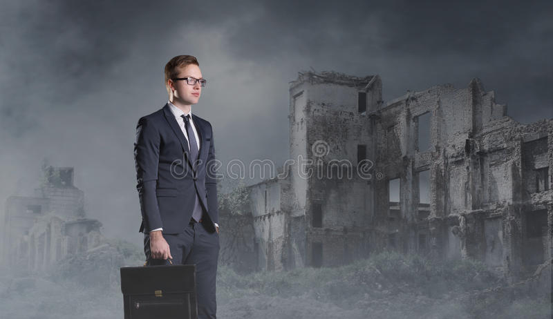 Businessman standing on apocalyptic background. Crisis, default, setback concept. stock photography