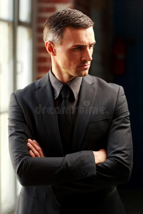 Businessman standing with arms folded. Pensive businessman standing with arms folded royalty free stock photography