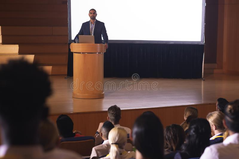 Businessman standing around the podium and giving speech in front of audience in the auditorium. Front view of handsome mixed race businessman giving speech in stock images