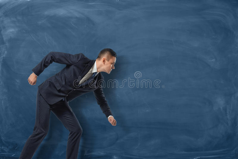 Businessman standing as if he is going to run or pursue his goal on the blue chalkboard background. royalty free stock photos